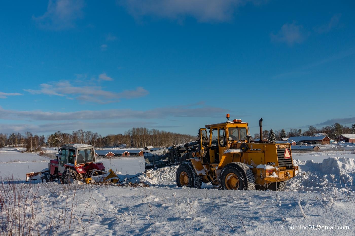Traktor och hjullastare i snön